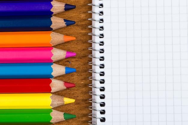 Werkplek. kladblok en kleurrijke potloden Gratis Foto