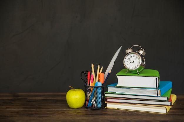 Werkplek met schoolboeken en wekker Gratis Foto