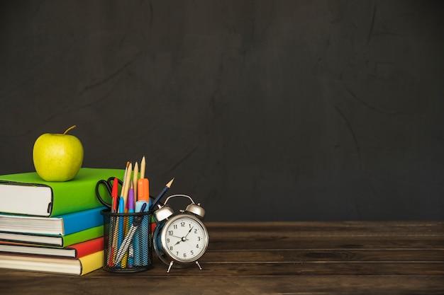Werkplek met schoolboeken voor leerboeken en wekker Gratis Foto