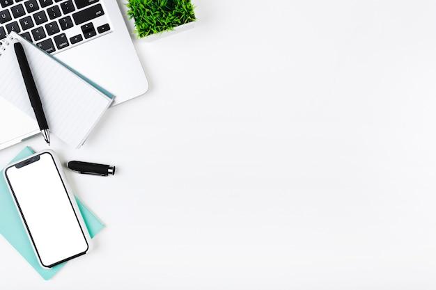 Werkplek met smartphonelaptop en notitieboekje Gratis Foto