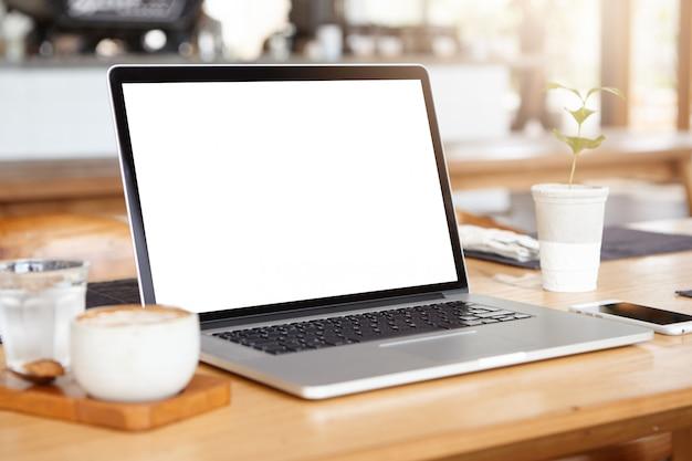 Werkplek van de zelfstandige: generieke laptop pc rustend op houten tafel met smartphone, mok koffie en glas water. Gratis Foto