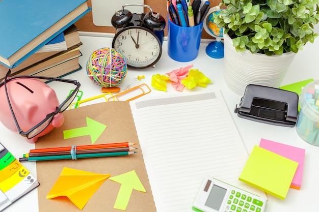Werkplek van een creatief persoon met een verscheidenheid aan kleurrijke kantoorbehoeftenobjecten Premium Foto