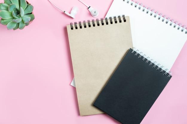 Werkruimte: blocnotes, hoofdtelefoons en succulente bloem op roze achtergrond. Premium Foto