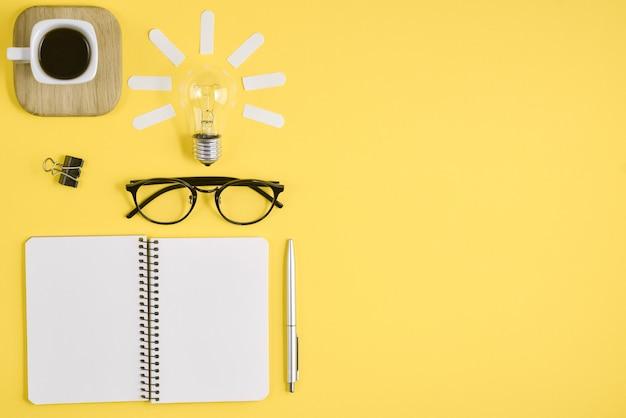 Werkruimte bureau stijl ontwerp kantoorbenodigdheden met pen, kladblok, brillen, kopje koffie en gloeilamp Premium Foto