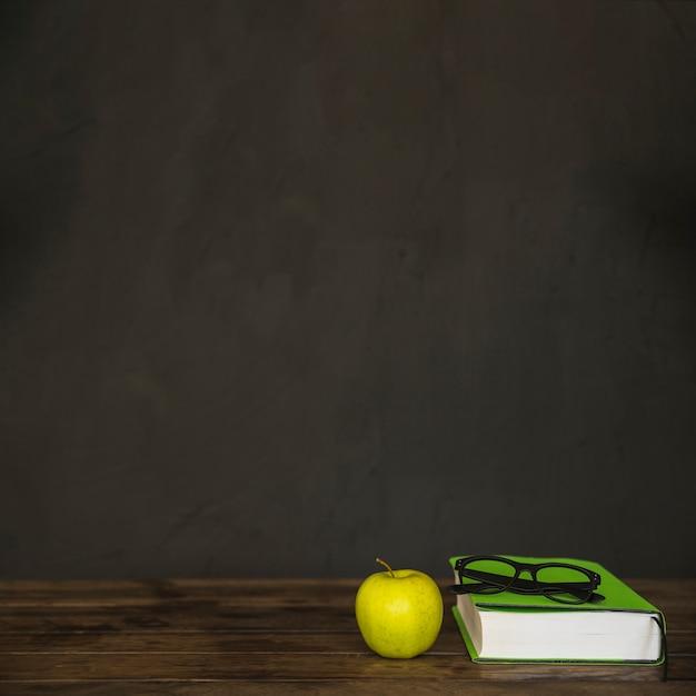 Werkruimte met boekglazen en appel Gratis Foto