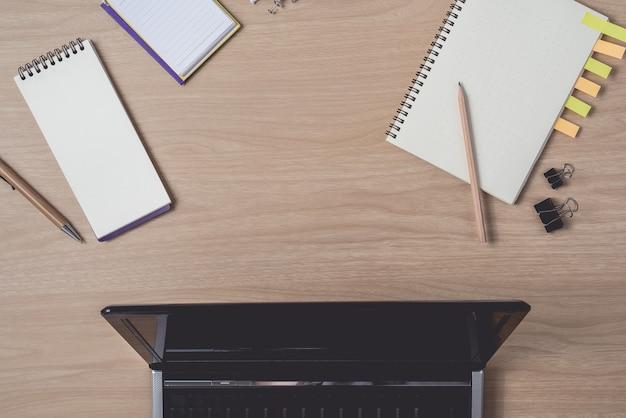 Werkruimte met dagboek of laptop en klembord, laptop, potlood, pen, plaknotities op houten Premium Foto