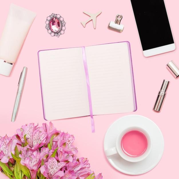 Werkruimte met dagboek, pen, smartphone, lippenstift, alstroemeria, theekop, cosmetica Premium Foto