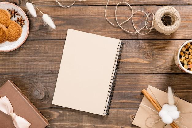 Werkruimte met kraft papier kladblok, touw, kopje thee, koekjes, geschenkdoos, vintage envelop. Premium Foto