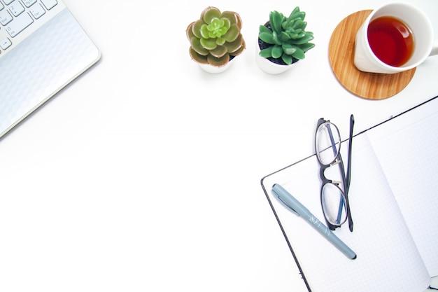 Werkruimte met laptop, notitieboekje, succulent sketchbook, kop thee op witte achtergrond. Premium Foto