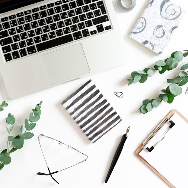Werkruimte met laptop, notitieboekjes, kalligrafiepen, eucalyptustakken, klembord, glazen Premium Foto