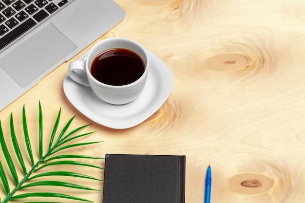 Werkruimte op kantoor, houten bureau met laptop en koffiemok bovenaanzicht Premium Foto