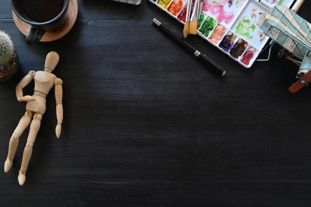 Werkruimte van de artiest met creatieve accessoires op een donkere houten tafel. werkruimte en kopieerruimte. Premium Foto