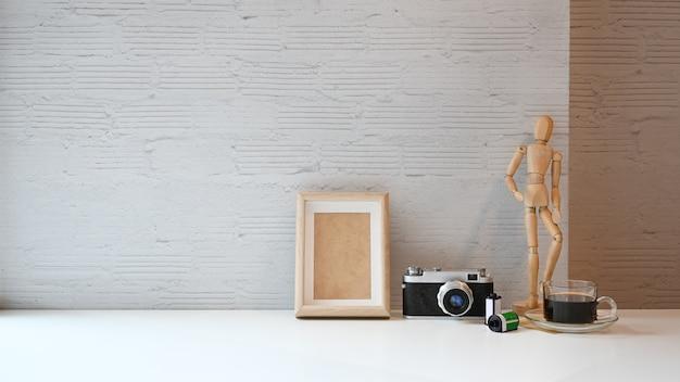 Werkruimtetafel camerafilm en filmrol, fotolijst en koffie op witte tafel. Premium Foto