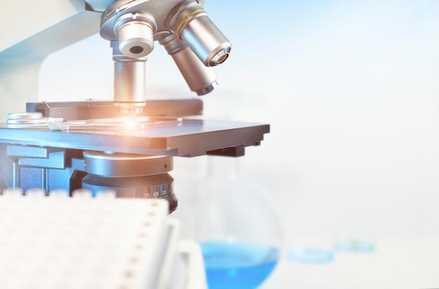 Wetenschappelijke achtergrond met close-up op lichte microscoop en vaag laboratorium Premium Foto