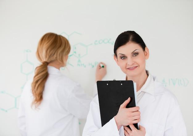 Wetenschapper die een formule schrijft die door haar medewerker wordt geholpen Premium Foto