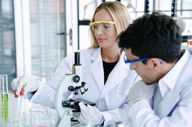 Wetenschappers die medische vloeistof met microscoop controleren terwijl het doen van gezondheidszorgonderzoek naar laboratorium Premium Foto
