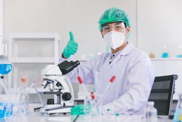 Wetenschappers in beschermende pakken in een wetenschappelijk laboratorium bestuderen een virus Premium Foto