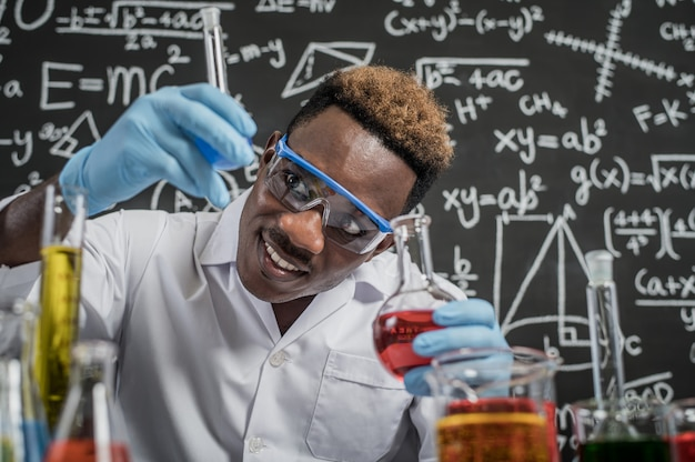 Wetenschappers kijken naar de hemelsblauwe chemicaliën in glas in het laboratorium Gratis Foto