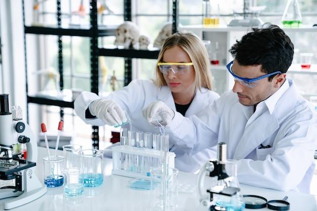 Wetenschappers maken testen met reageerbuis terwijl ze onderzoek doen naar wetenschappelijk laboratorium Premium Foto