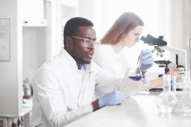 Wetenschappers werken nauw samen met de microscoop in het laboratorium door experimenten en analyses uit te voeren. Gratis Foto