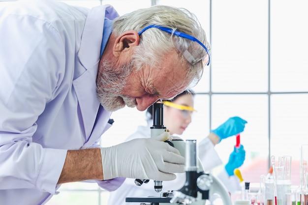 Wetenschapsmensen die met microscopenchemische producten werken in laboratorium Premium Foto