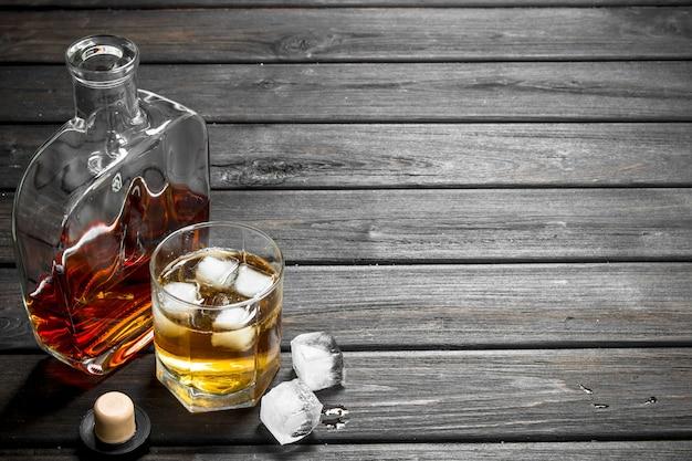 Whisky in een glazen fles en een glas. op houten Premium Foto