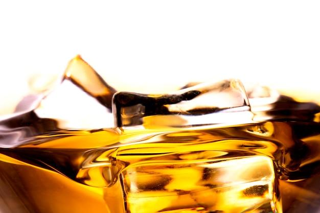 Whisky in glas met ijsblokje. op de rots Premium Foto