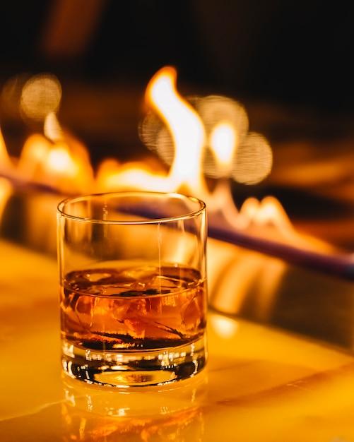 Whisky met ijsblokjes boven open haard Gratis Foto