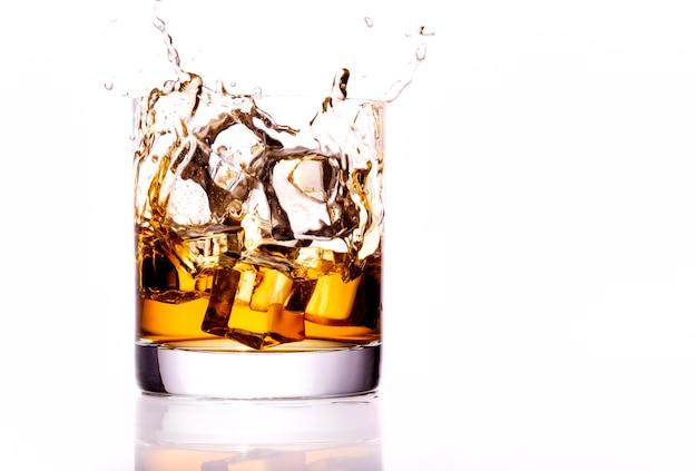 Whiskyglas met plons, op witte achtergrond wordt geïsoleerd die Premium Foto