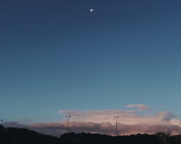 Wide shot van een halve maan aan de hemel over de grijze wolken Gratis Foto