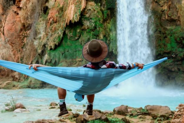 Wide shot van een man liggend op een hangmat naast een waterval stroomt naar beneden van een heuvel Gratis Foto