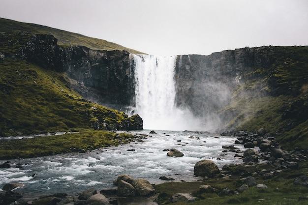 Wide shot van een prachtige waterval in de groene heuvels Gratis Foto