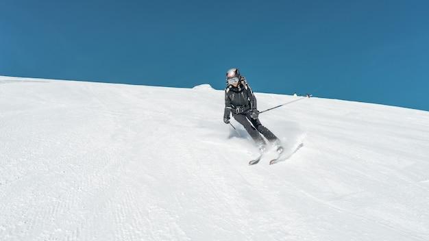 Wide shot van een skiër skiën op een besneeuwde ondergrond ski-outfit en helm dragen Gratis Foto
