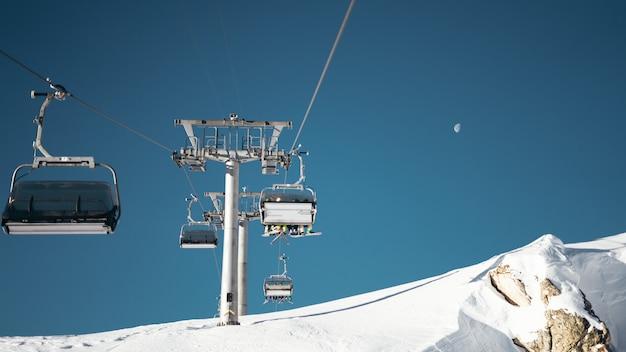 Wide shot van kabelbanen en grijze pilaar op een besneeuwde ondergrond onder een heldere blauwe hemel met een halve maan Gratis Foto
