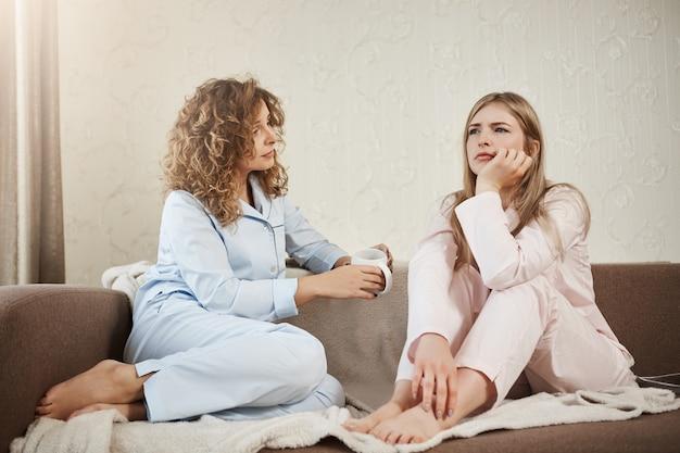 Wie heeft psycholoog nodig als je beste vriend hebt. twee vrouwen zitten op de sofa in nachtkleding in gezellige kamer, bespreken persoonlijke problemen, gericht en lastig gevallen met probleem. meisje probeert vriendin te troosten Gratis Foto