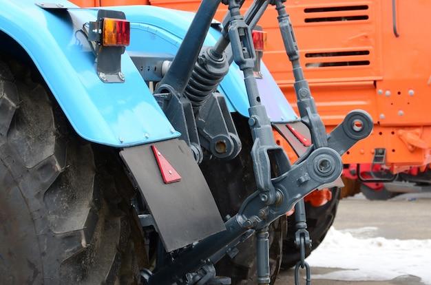 Wielen van achtermening van nieuwe tractor in sneeuwweer. achteraanzicht van landbouwvoertuig Premium Foto