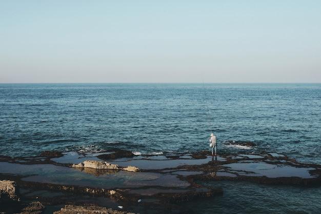 Wijd geschoten van een visser die zich op de kust overdag bevindt Gratis Foto