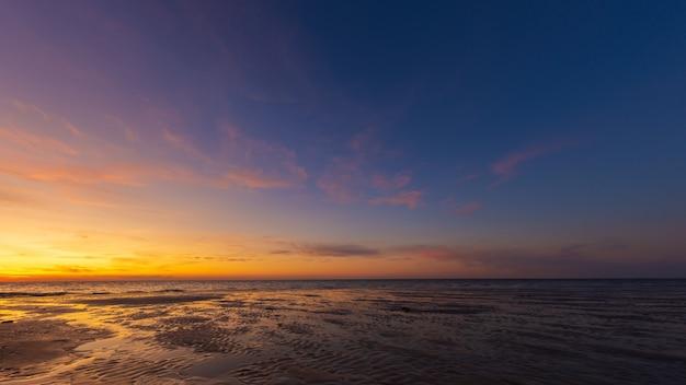 Wijd geschoten van natte strandkust onder een blauwe en gele hemel bij zonsondergang Gratis Foto