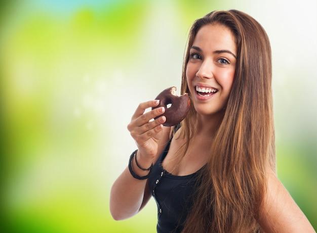 Wijd glimlachende vrouw met een donut Gratis Foto