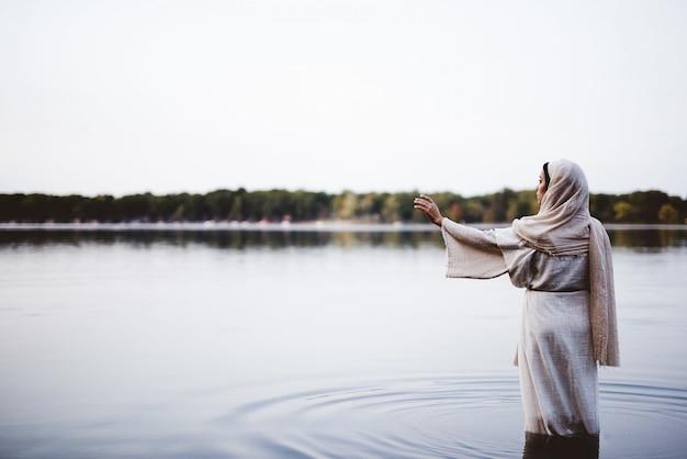 Wijfje dat een bijbels kleed draagt en zich in het water met haar omhoog hand bevindt Gratis Foto