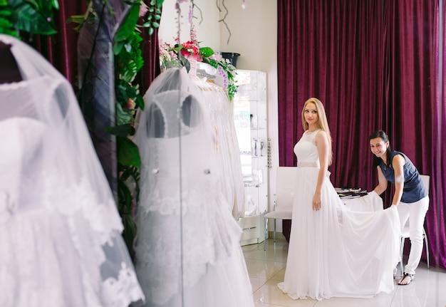 Wijfje dat op huwelijkskleding probeert in een winkel met vrouwenmedewerker. Premium Foto