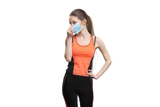 Wijfje in een gezichtsmasker en een oranje sportkostuum dat uitwerkt Gratis Foto