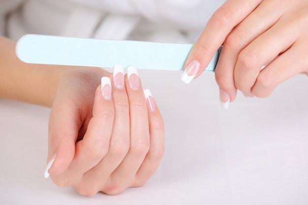 Wijfje polijsten haar vingernagels met een franse manicure Gratis Foto