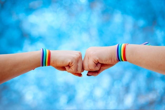 Wijfjes die handteken met de armband van regenboogkleuren op onscherpe achtergrond maken Premium Foto