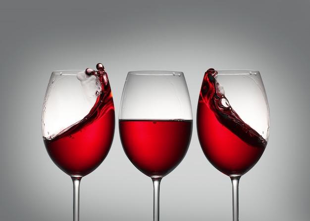 Wijn. drie glazen rode wijn met plons in zijglazen die symmetrie vormt. Premium Foto