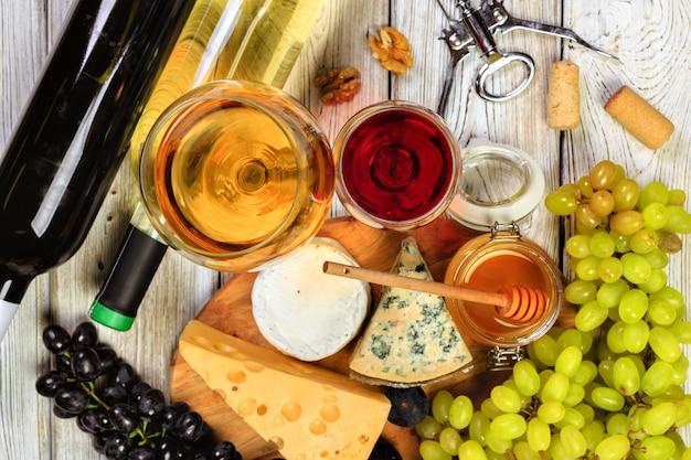 Wijn met takken van witte druiven. op een houten tafel. Premium Foto