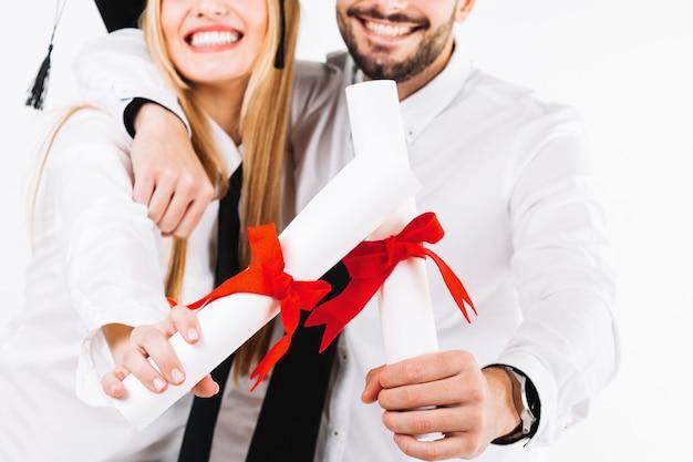 Wijs vrolijke mensen met diploma's bij Gratis Foto