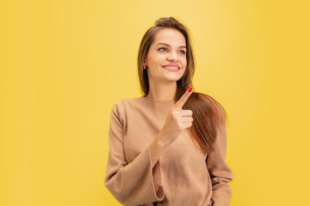 Wijzend. portret van jonge blanke vrouw geïsoleerd op geel Gratis Foto