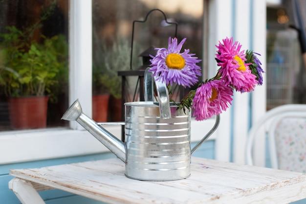 Wildflowers in gieters op witte lijst in tuin. tuingereedschap, kamerplanten en bloemen op terras. Premium Foto