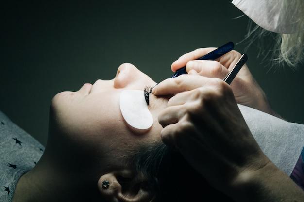 Wimper extensions. close-up van kunstmatige wimpers met pincet. Premium Foto